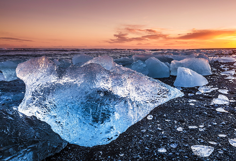 Broken ice from washed up icebergs on Jokulsarlon black beach at sunset, Jokulsarlon, southeast Iceland, Iceland, Polar Regions