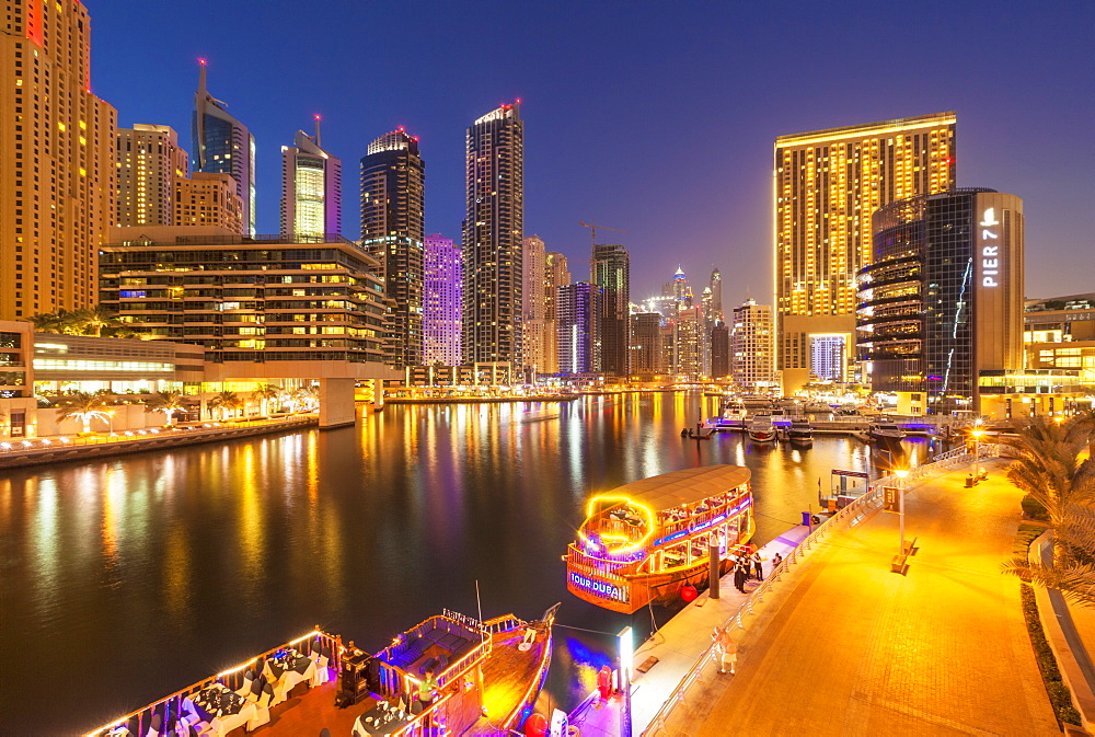 Dubai Marina skyline and tourist boats at night, Dubai City, United Arab Emirates, Middle East