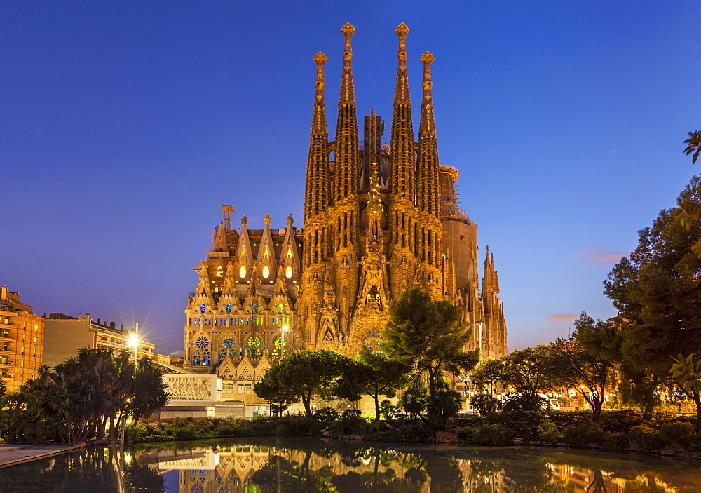 La Sagrada Familia church lit up at night designed by Antoni Gaudi, reflected in pool, Barcelona, Catalonia, Spain, EU, Europe