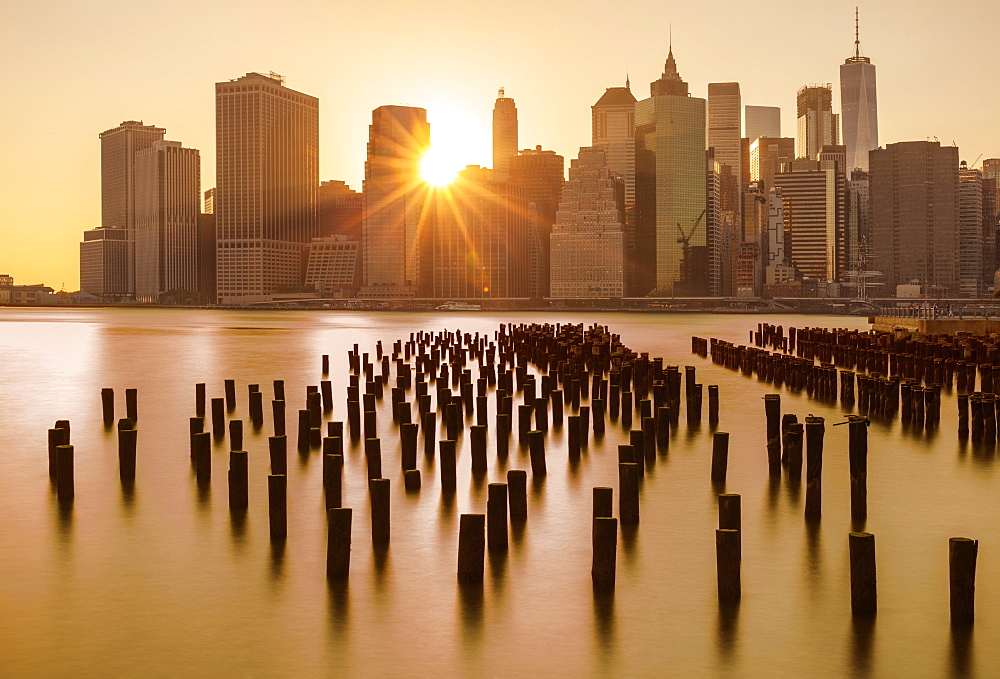 Lower Manhattan skyline, New York skyline, exposed wooden pier stumps, at sunset, East River, New York, United States of America, North America