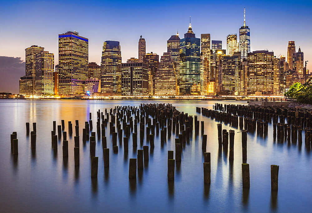 Lower Manhattan skyline, New York skyline, exposed wooden pier stumps, at night, East River, New York, United States of America, North America