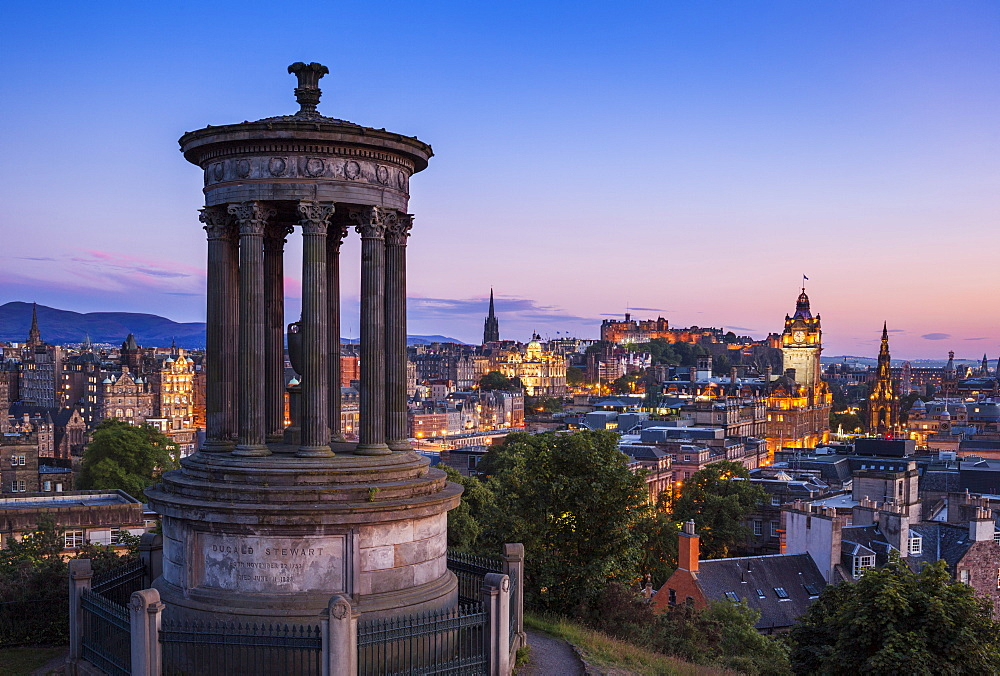 Dugald Stewart Monument, city centre and Edinburgh skyline at sunset, Calton Hill, Edinburgh, Midlothian, Scotland, United Kingdom, Europe