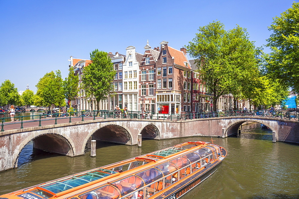 Canal tour boat at the junction of Leidsegracht canal bridge and Keizergracht canal Amsterdam Netherlands Holland EU Europe