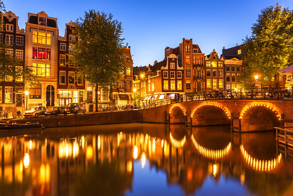 Illuminated canal bridge with reflections at night over the Singel Torensluis canal, Amsterdam, North Holland, Netherlands, Europe - 698-3372
