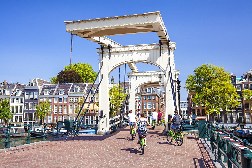 Cyclists riding across the Magere brug (Skinny Bridge) spanning the River Amstel, Amsterdam, North Holland, Netherlands, Europe - 698-3373