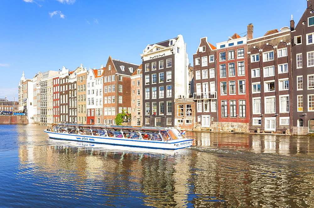 Row of typical Dutch houses on Damrak Canal with canal tour boat, Amsterdam, North Holland, Netherlands, Europe