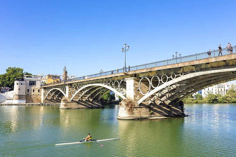 Rower going under the Triana bridge over the Guadalquivir River, Triana district, Seville, Spain, Andalusia, Spain, Europe