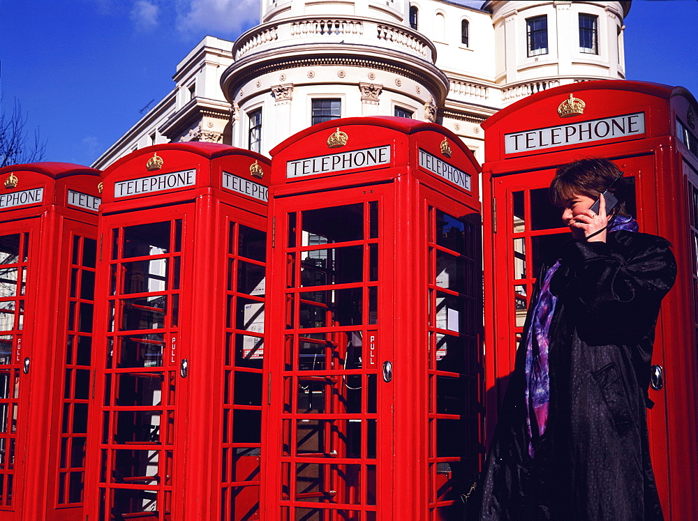 Woman outside red phone boxes using mobile phone, London