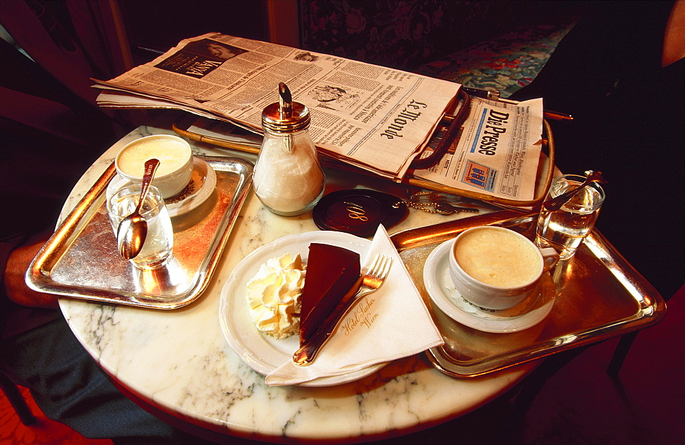 Coffee desserts and a newspaper on a table in the Sacher Cafe