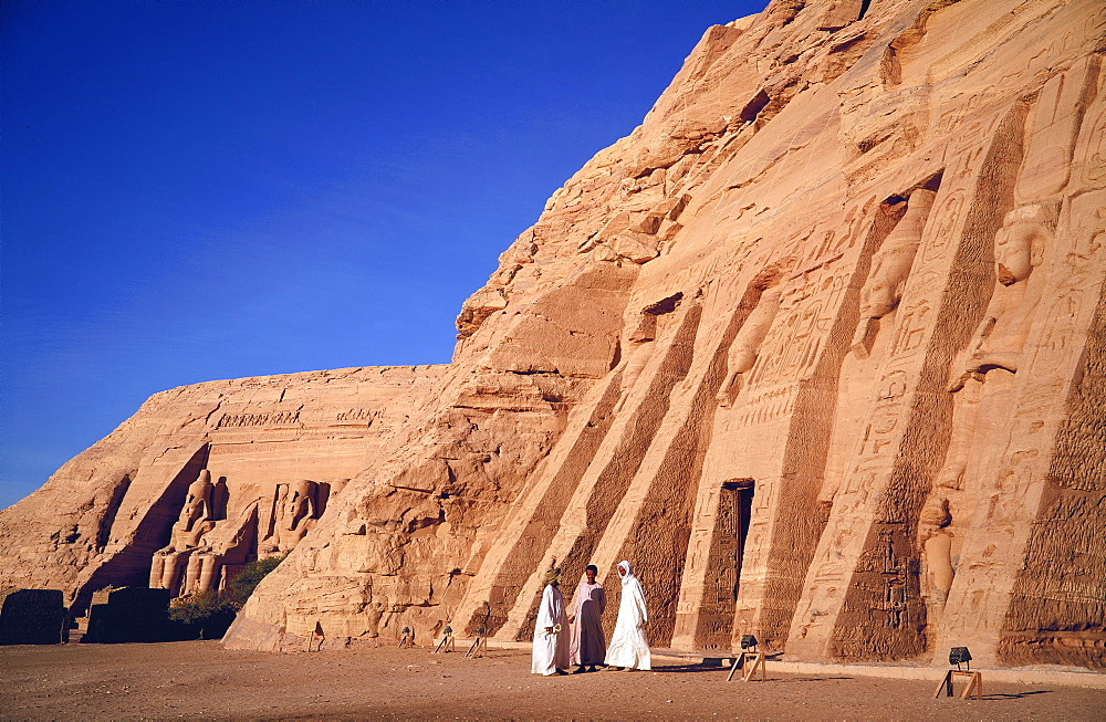Three traditionally dressed men outside the Temple of Hathor, built in honour of Queen Nefertari, and in the background the colossi of Ramses II, outside the Temple of Re-Herakhte, built for Ramses II, (also known as the Sun or Great Temple of Ramses II), Abu Simbel, (moved to current site when the Aswan High Dam was built), Nubia, Egypt, Africa