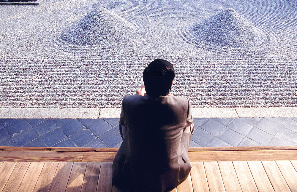 Figure sat comtemplating Zen garden, Kyoto, Japan