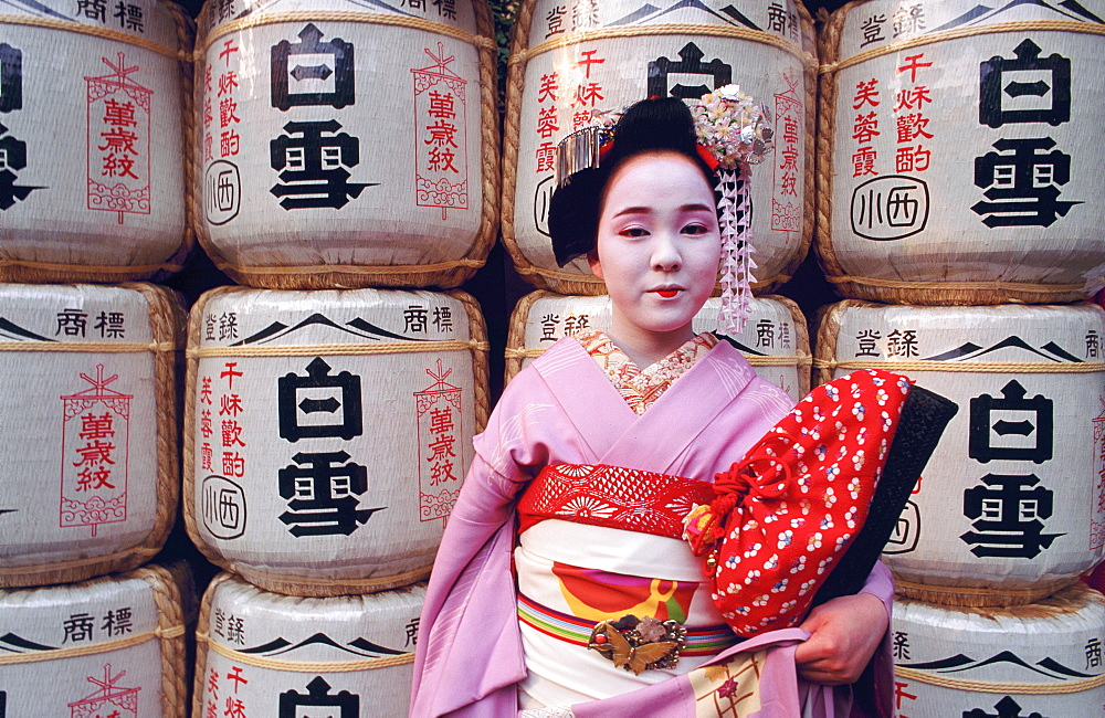 Portrait of a Maiko (a geisha's apprentice) in front of temple lanterns, Kyoto, Japan - 701-192
