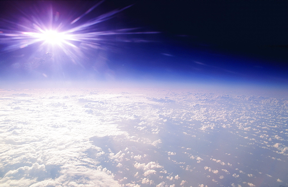 Aerial view over ocean and clouds, from high atmosphere, with distorted sun