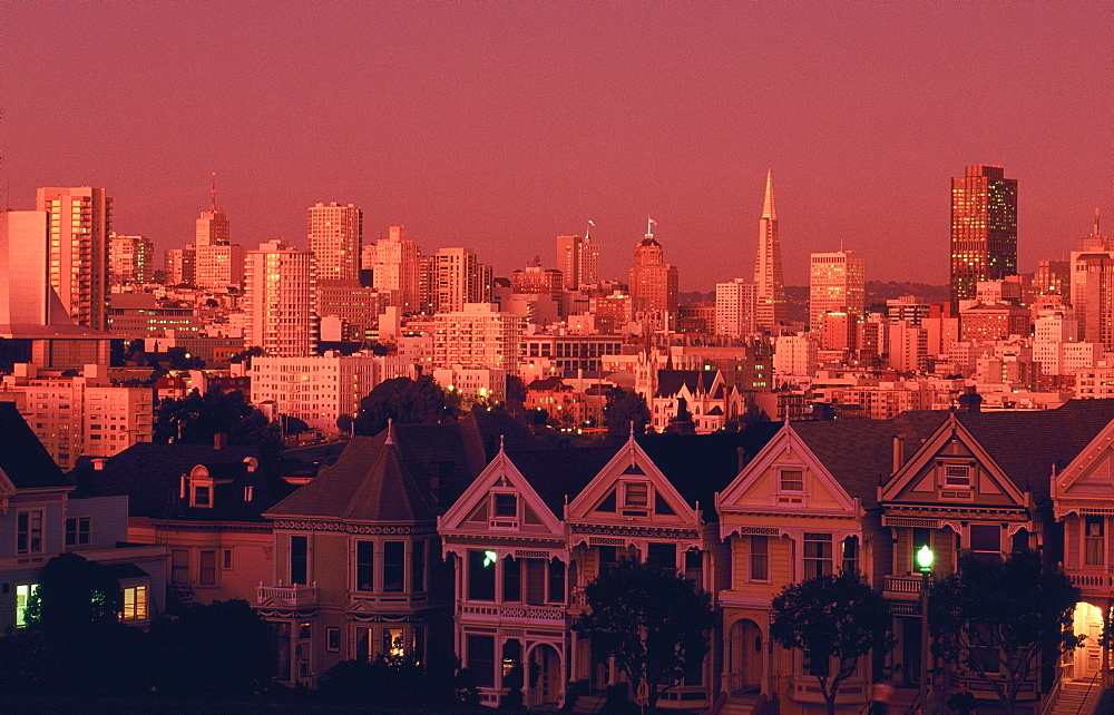 The famous Victorian Painted Ladies of Steiner Street, Alamo Square, with city skyline at dusk, San Francisco, California, USA