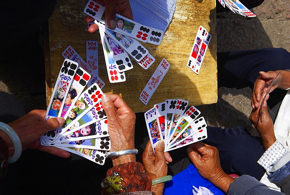 Naxi women playing a local game of cards, Lijiang, Yunnan, China, Asia  - 712-2585