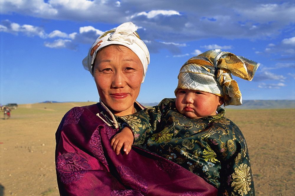 Head and shoulders portrait of a smiling nomad woman and child in traditional clothing, looking at the camera, at Naadam Festival, Altai, Gov-altai, Mongolia, Central Asia, Asia
