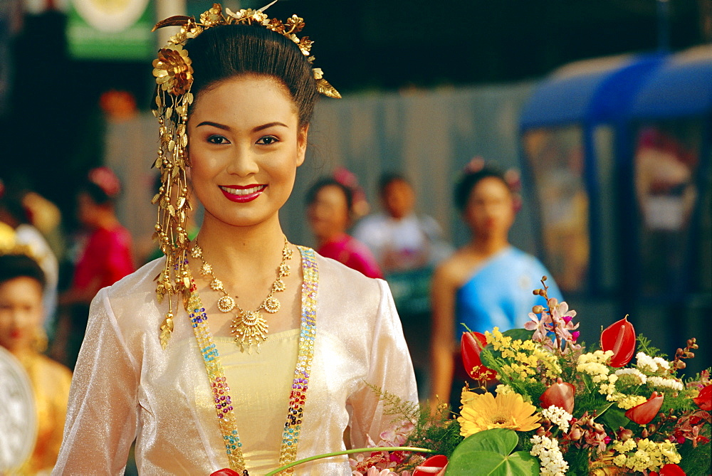Portrait of a young Thai 'queen' holding flowers competing for 'Flower Festival Queen' title, Chiang Mai, Thailand