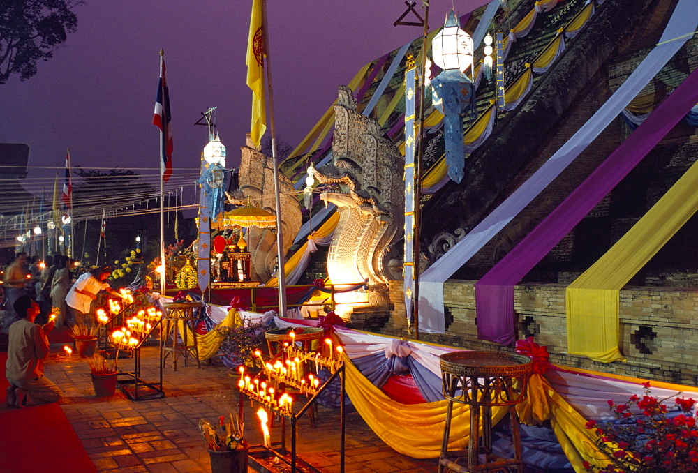 People worshipping during Buddhist festival at the foot of temple chedi, Wat Chedi Luang, Chiang Mai, Thailand, Southeast Asia, Asia