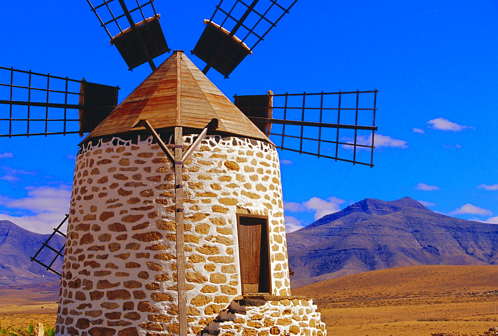 Old Windmill with volcanoes in background near Tefia, Fuerteventura, Canary Islands, Spain - 718-330