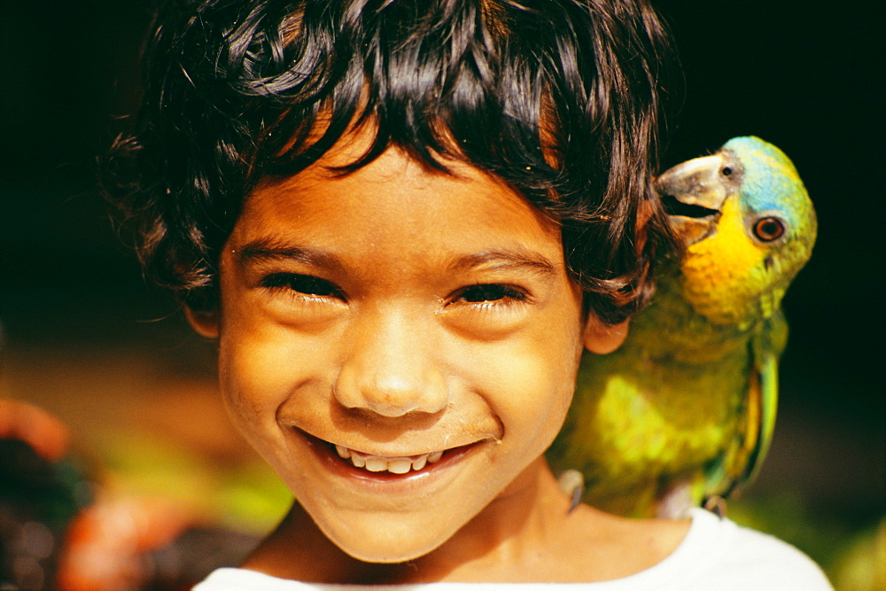 Head and shoulders portrait of a young boy with pet parrot, West Indies, Caribbean, Central America - 728-1162