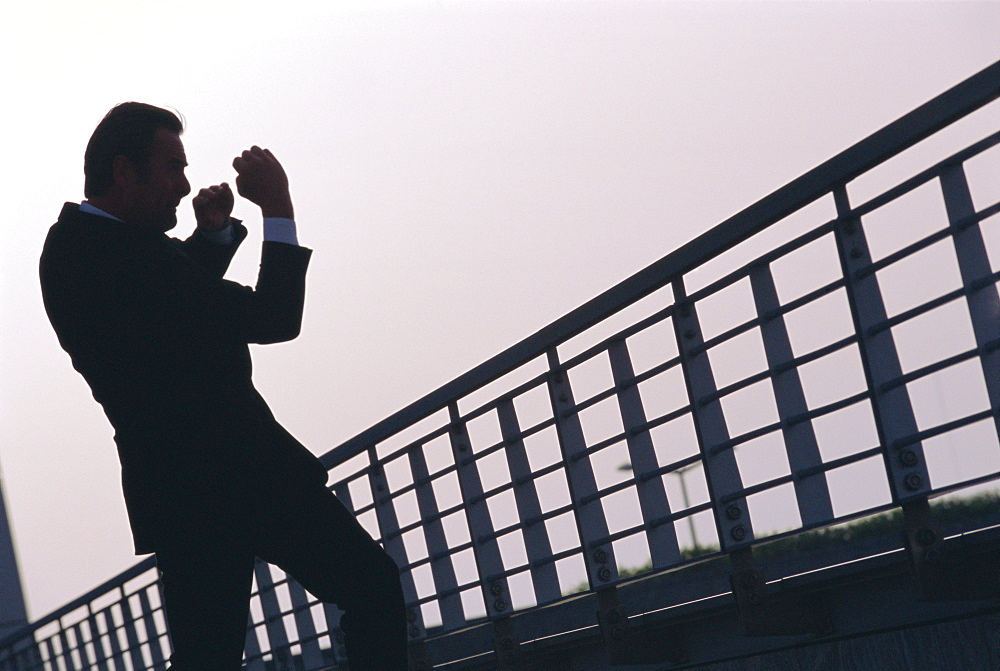 A business man outdoors shadow boxing near railings