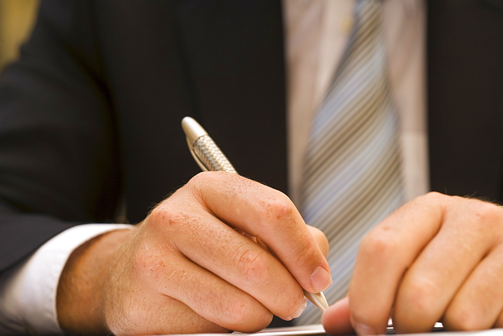 Hands, signing a paper