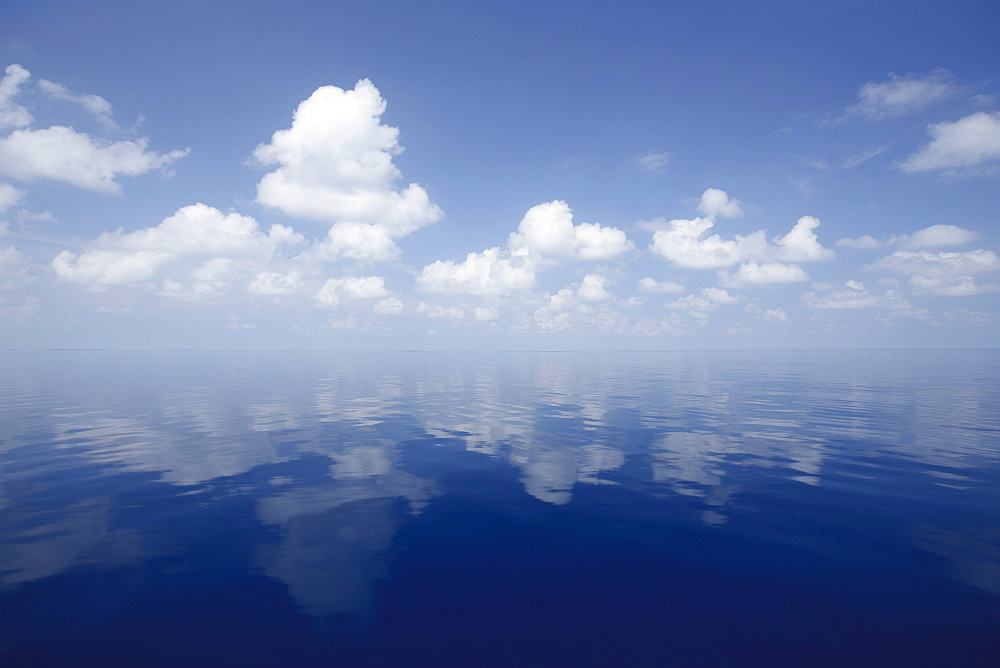 Still ocean reflecting sky and clouds, Maldives, Indian Ocean, Asia