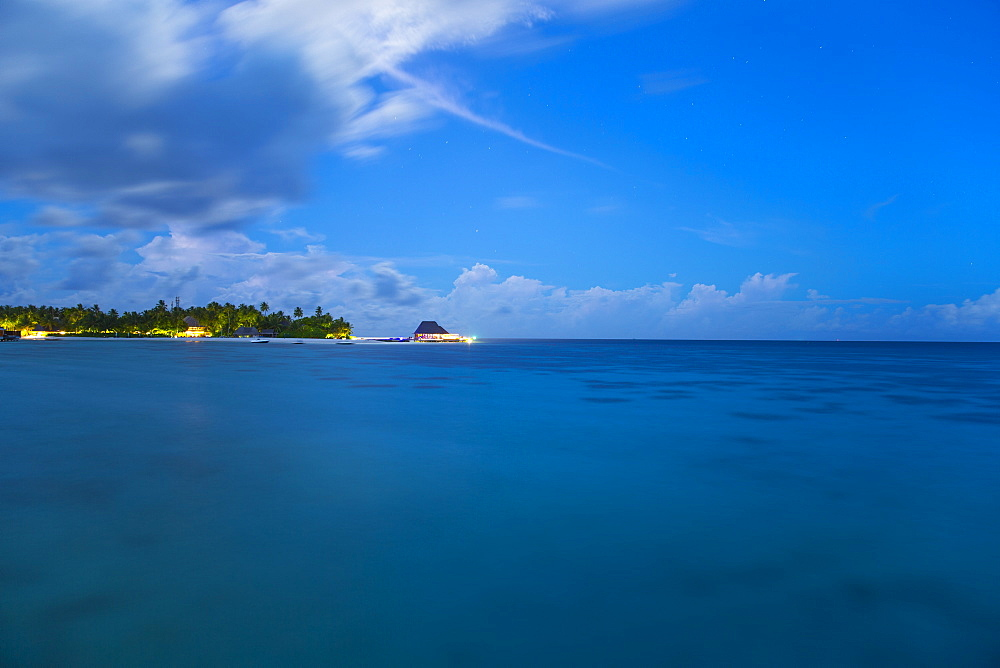 Calm ocean and tropical island at night, The Maldives, Indian Ocean, Asia