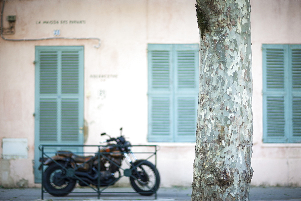 Old motorbike next to shuttered building, St. Tropez, Var, Provence, Cote d'Azur, France, Europe
