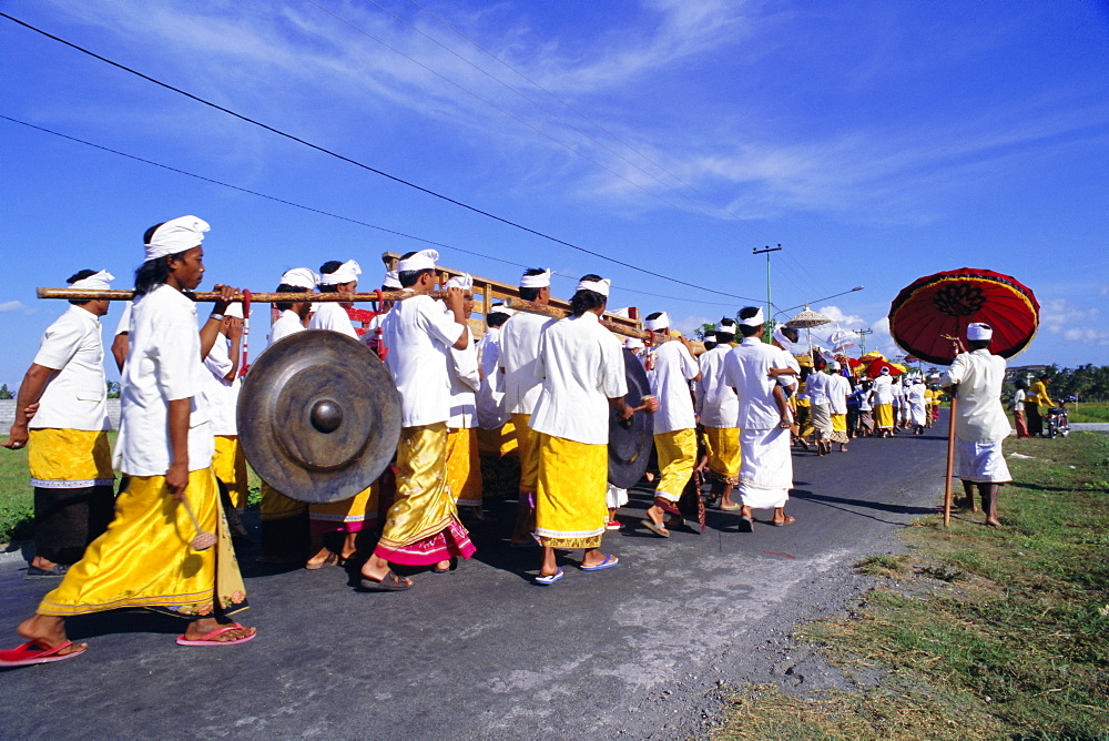Procession including men carrying a large gong at a ceremony, island of Bali, Indonesia, Southeast Asia, Asia