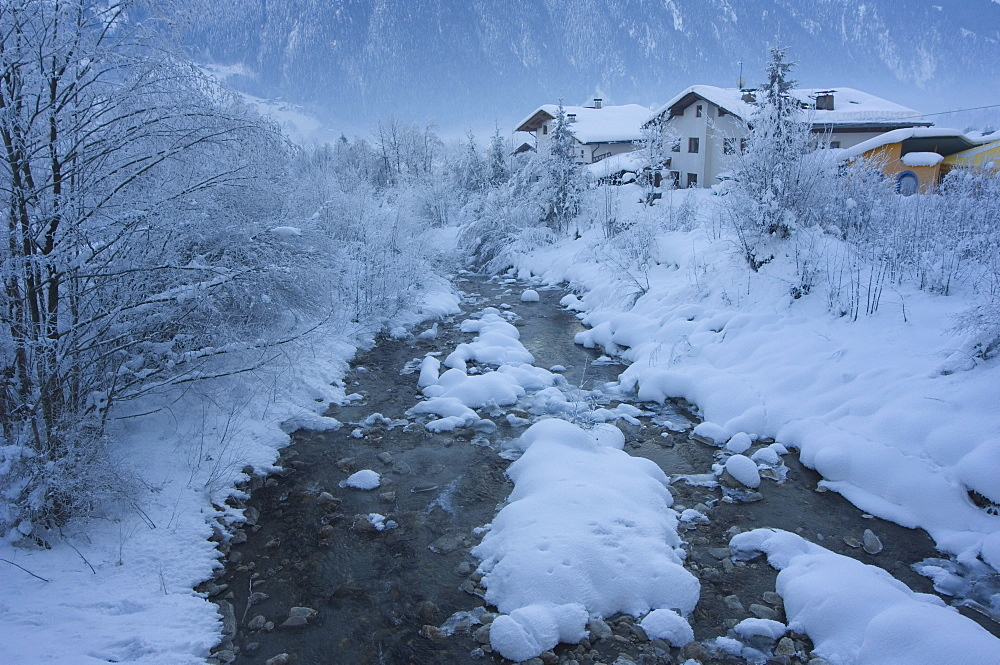 Snow covered river and houses, Mayrhofen ski resort, Zillertal Valley, Austrian Tyrol, Austria, Europe