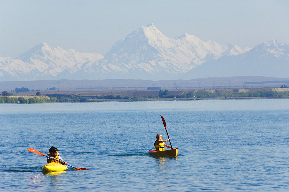 Kayaking on Lake Benmore and a distant Aoraki (Mount Cook), 3754m, Australasia's highest mountain, Southern Alps, Mackenzie Country, Otago, South Island, New Zealand, Pacific