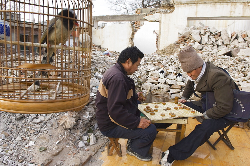 Men playing a board game in a neighbourhood Hutong partially destroyed and marked for demolition, Beijing, China, Asia