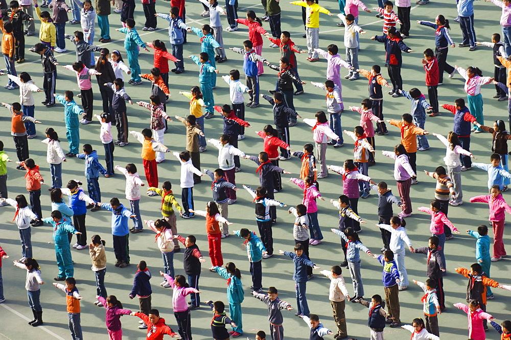 Junior school children exercising in colourful clothes, Beijing, China, Asia