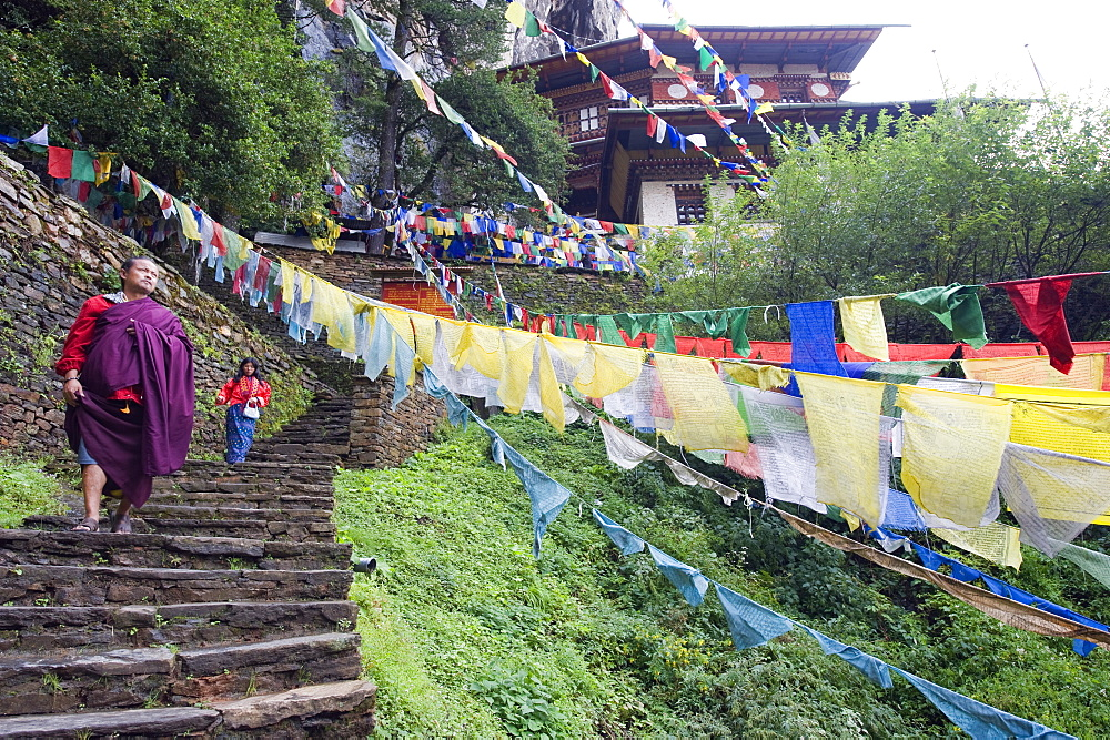 A monk walking through prayer flags, Tigers Nest, Taktsang Goemba, Paro Valley, Bhutan, Asia