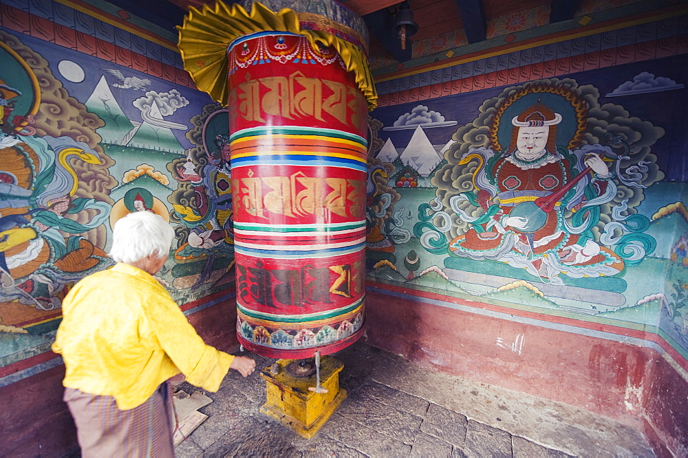 A woman spinning a prayer wheel, Chimi Lhakhang dating from 1499, Temple of the Divine Madman Lama Drukpa Kunley, Punakha, Bhutan