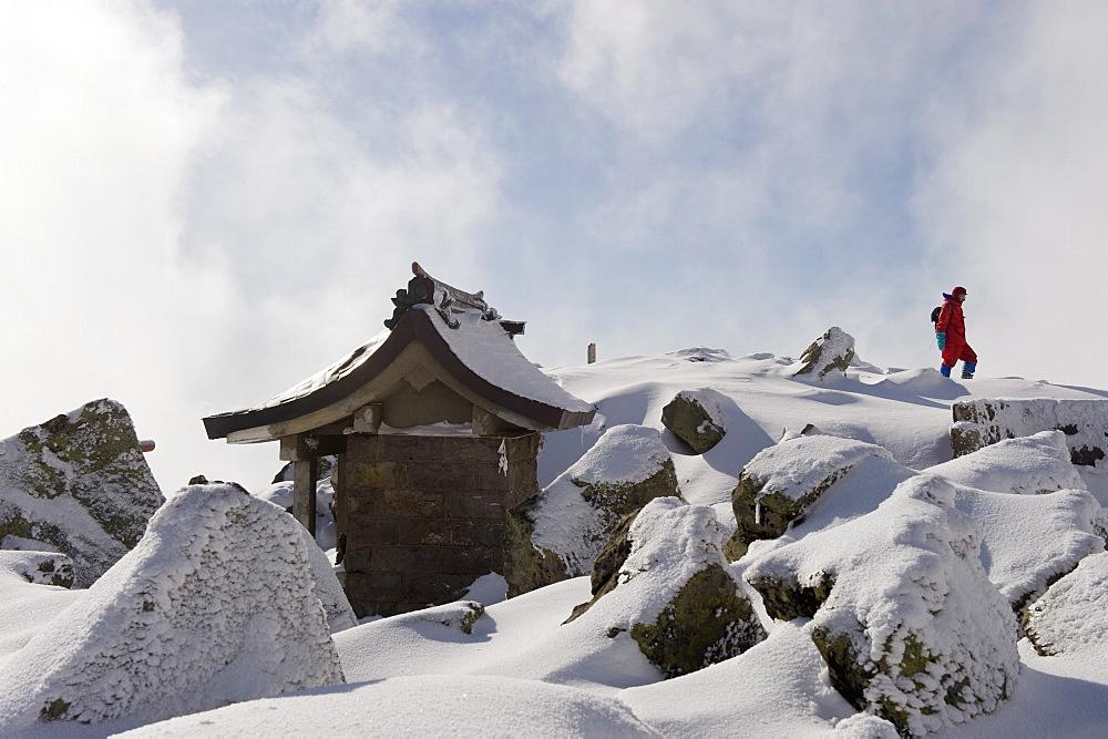 Shrine and climber on snow covered Iwaki San mountain, Aomori prefecture, Japan, Asia