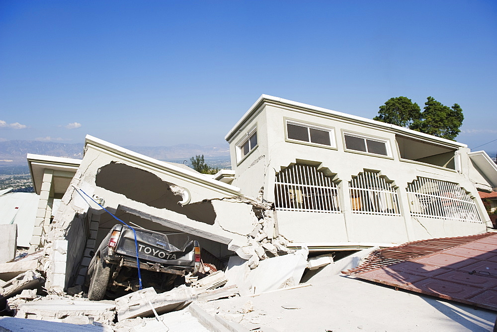 Damaged car and buildings, January 2010 earthquake, Montana Estate, Port au Prince, Haiti, West Indies, Caribbean, Central America