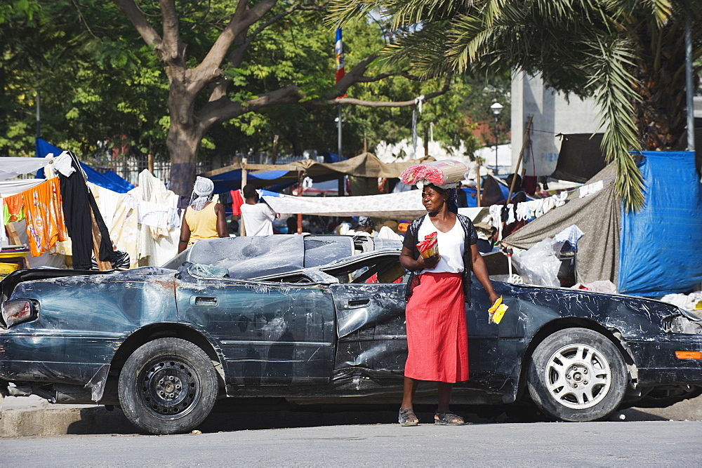 Woman in front of a damaged car, January 2010 earthquake, downtown, Port au Prince, Haiti, West Indies, Caribbean, Central America
