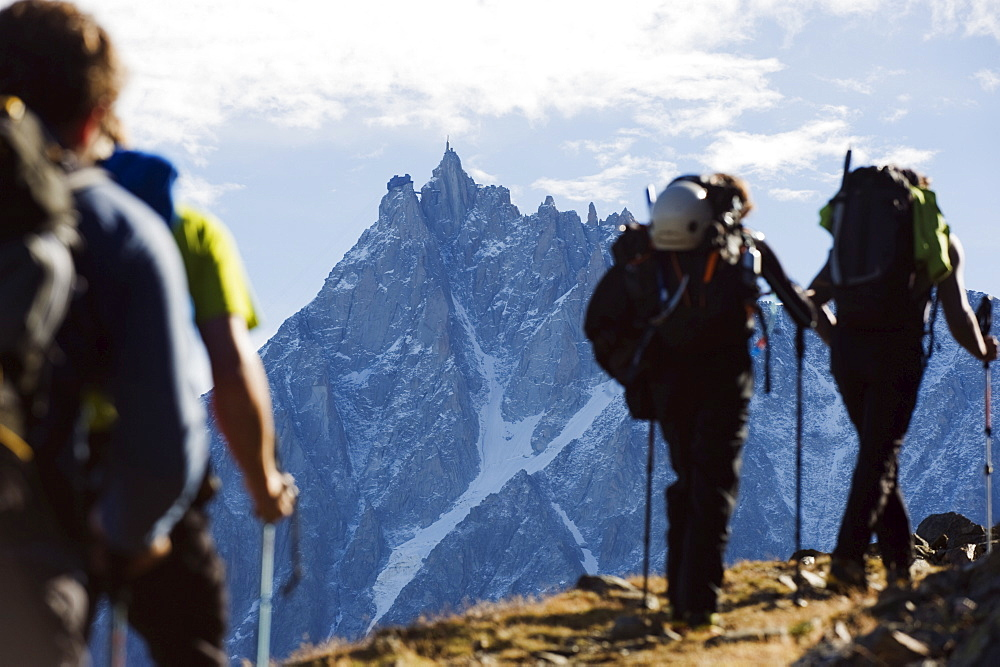 Hikers on Mont Blanc against mountain backdrop of Aiguille du Midi, Chamonix, French Alps, France, Europe