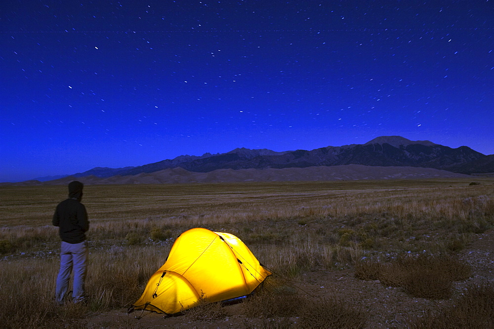 Hiker and tent illuminated under the night sky, Great Sand Dunes National Park, Colorado, United States of America, North America