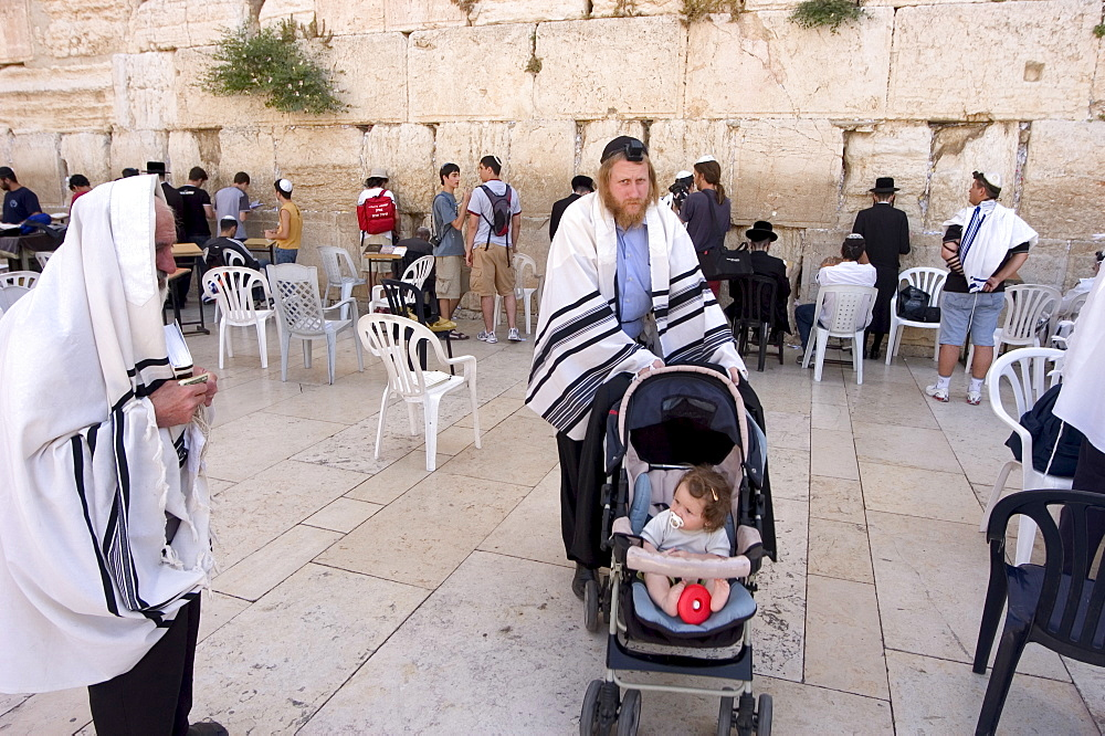 Jewish man with child in pram, praying at the Western Wailing Wall, Old Walled City, Jerusalem, Israel, Middle East