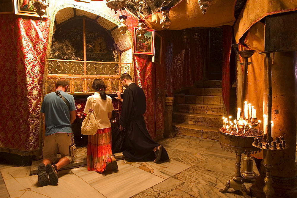 Priest and tourists praying in the Church of the Nativity (birth place of Jesus Christ), Bethlehem, Israel, Middle East