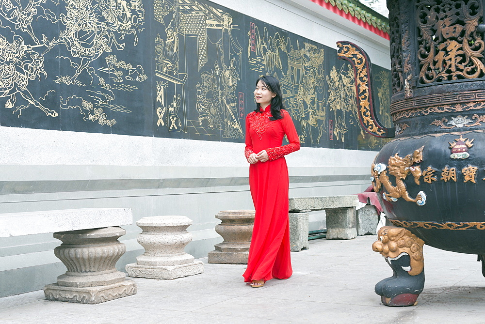 Woman wearing aoi dai dress, Nghia An Hoi Quan Pagoda, Cholon, Ho Chi Minh City (Saigon), Vietnam, Indochina, Southeast Asia, Asia