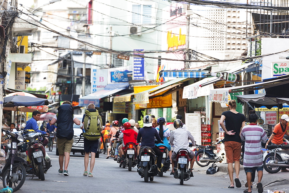 Backpackers on city street, Ho Chi Minh City (Saigon), Vietnam, Indochina, Southeast Asia, Asia