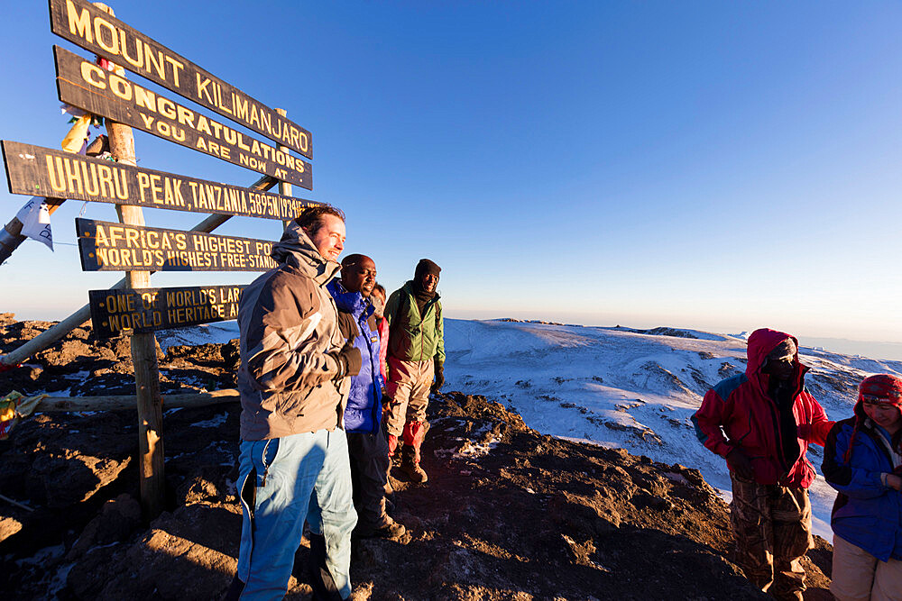 Climbers at summit sign and views on Mount Kilimanjaro, Kilimanjaro National Park, UNESCO World Heritage Site, Tanzania, East Africa, Africa