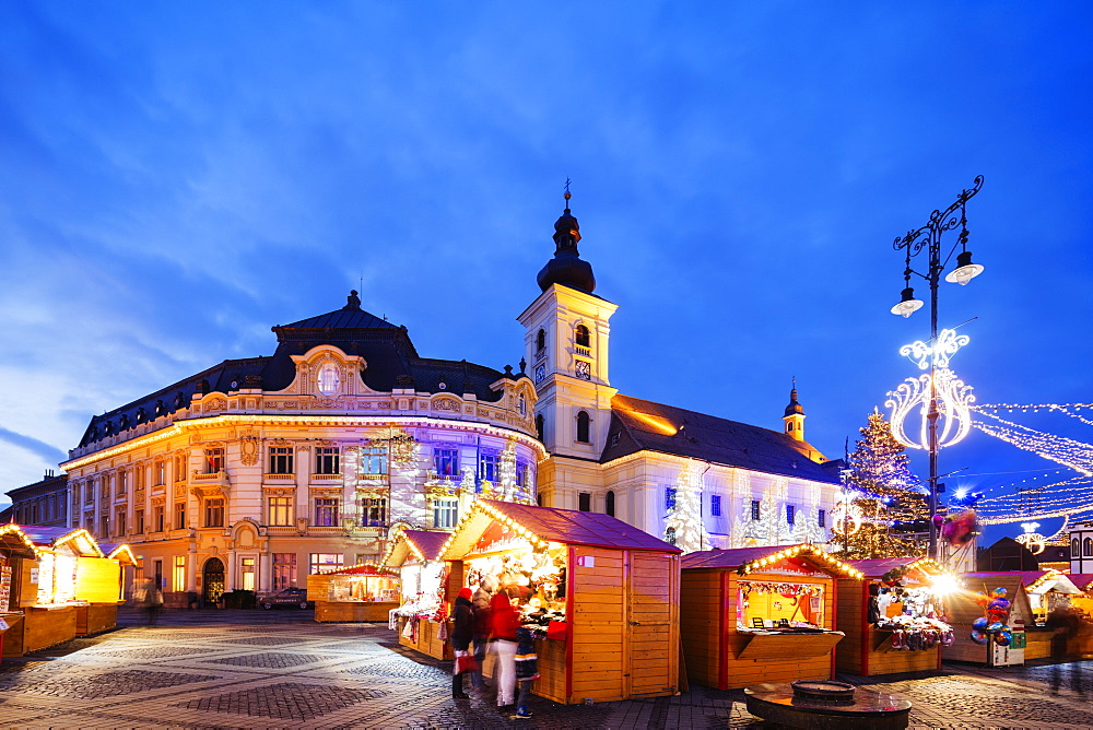 Christmas market in Plaza Piata Mare, City Hall and Baroque Jesuit Church, Sibiu, Romania, Europe