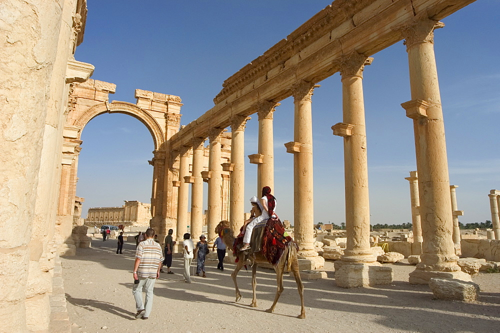 Tourist camel ride, monumental arch, archaelogical ruins, Palmyra, UNESCO World Heritage Site, Syria, Middle East