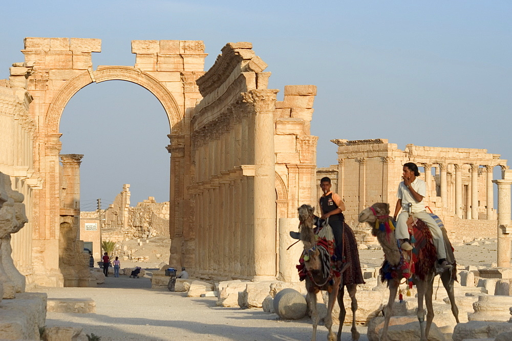 Young men on camels, monumental arch, archaelogical ruins, Palmyra, UNESCO World Heritage Site, Syria, Middle East