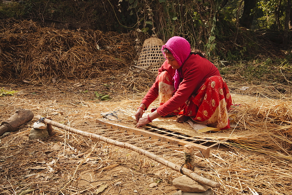 Local woman making traditional woven bed using grass, Pokhara, Nepal, Asia - 734-194